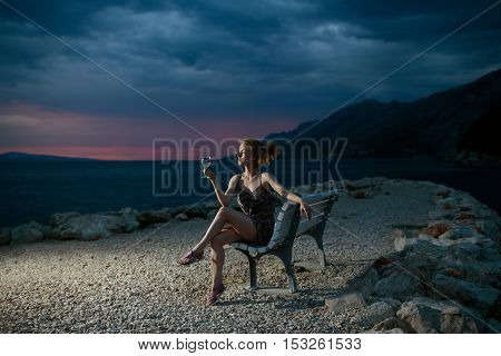 pretty sexy woman or girl with wine glass sits on bench outdoor over dark twilight sky with clouds on beach with sea or ocean water on evening natural background