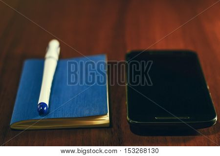 Pocket book pen and mobile smart phone on wooden table