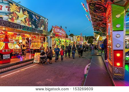 ALBA, ITALY - OCTOBER 10, 2015: People walking by illuminated attractions at Luna Park - traditional amusement park taking place each year on october during International White Truffle Festival.