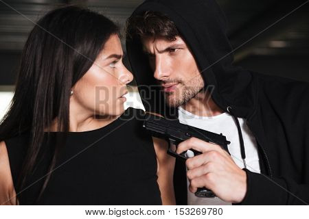Closeup of scared young woman threatened with gun by criminal man in hoodie