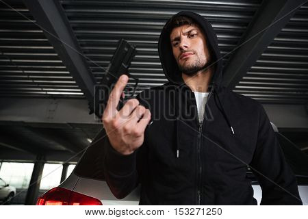 Serious young criminal man in hoodie holding gun on car parking