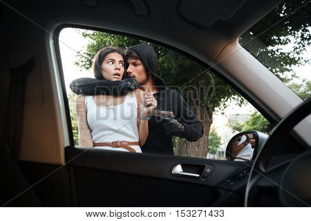 Aggressive young man robber threatening with gun and stealing car of frightened young woman outdoors
