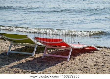 Green and red empty sunbed on the beach in a beautiful summer day