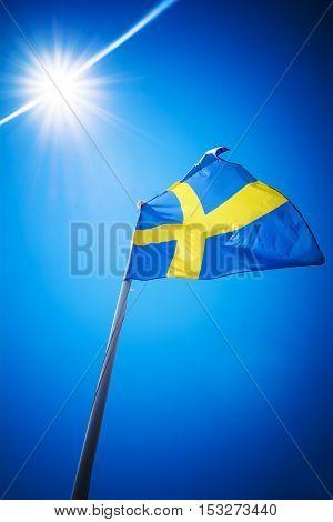 Sweden flag against blue sky in bright sunshine