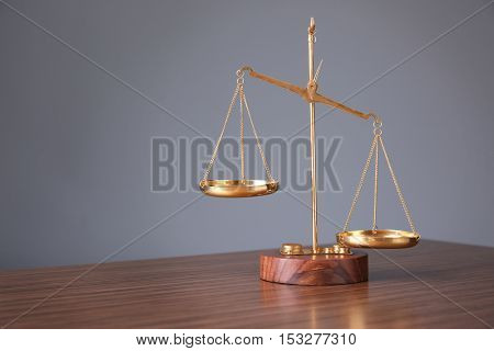 Justice scales on wooden table and  grey background