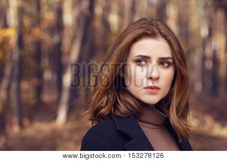 Fashion style portrait of young beautiful woman in black coat. Beautiful sad girl in autumn clothes. Close-up fashion portrait of beautiful brunette woman outdoors