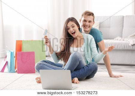 Happy couple with credit card and laptop sitting on floor and making shopping