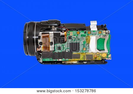 Disassembled compact camcorder. Close-up. Isolated on blue background.