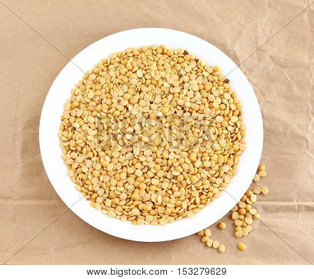 Toor dal, also known as split pigeon pea, rich in proteins, in a plate on a crumpled brown paper background.