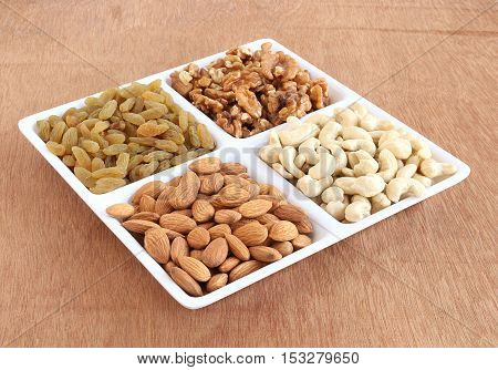 Healthy food almonds, cashew nuts, walnuts and raisins in a plate.