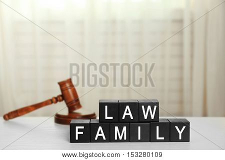 Black cubes with phrase LAW FAMILY and gavel on white table