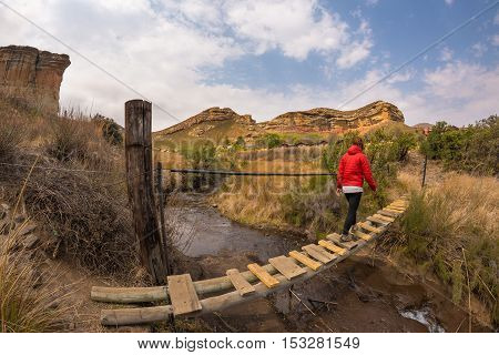 Woman Hiker Crossing Hanging Footbridge, Suspended On Stream, In The Majestic Golden Gate Highlands