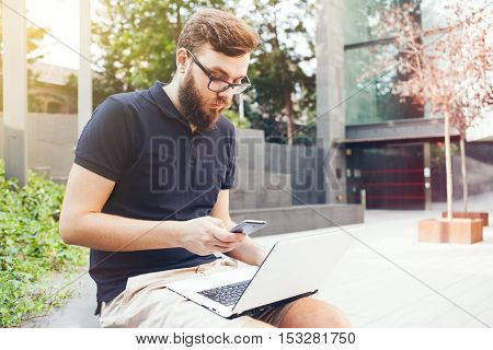 Young man with hipster beard is working outdoors on laptop computer while sitting in city square. Doing business call. Nice weather, sun light flair