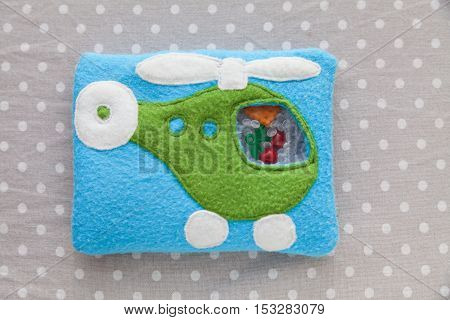 Children's soft toy blue helicopter of colored fleece for motor development. Bag fleece filled with plastic beads and figurines on a background of gray fabric in white peas. handmade toys. Happy childhood.