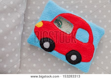 Children's soft toy red car of colored fleece for motor development. Bag fleece filled with plastic beads and figurines on a background of gray fabric in white peas. handmade toys. Happy childhood.