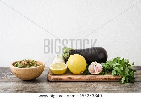 Baba ganoush and ingredients on wooden table