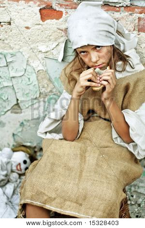 Sad child wearing vintage, dirty clothing, with a piece of bread in her hand and smiling doll. More available.