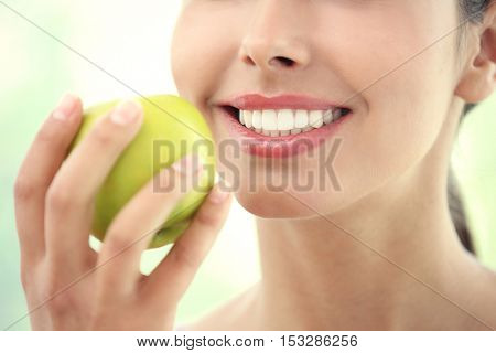 Young woman eating fresh apple, close up