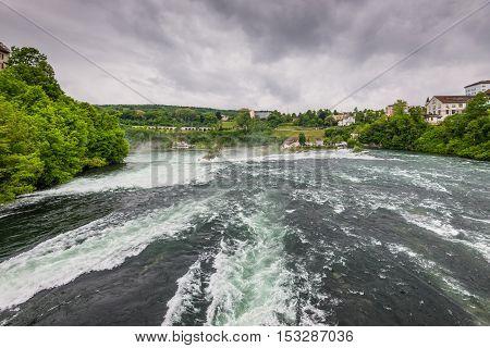 Rhine Falls in cloudy weather in Neuhausen am Rheinfall Schaffhausen Switzerland. The Rhine Falls is the largest waterfall in Europe.
