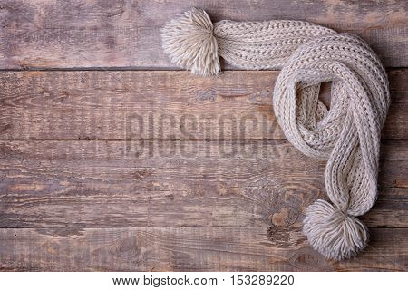 White knitted scarf with pompons on wooden background
