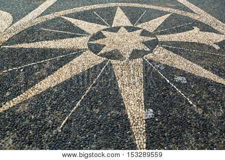 Beautiful large patterned pebble stone mosaic arranged in a symbol on pavement pedestrian street in Genova, Liguria, Italy