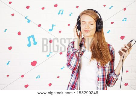 Joyful young woman with smartphone and headphones on light background with musical notes and hearts. Music lover concept