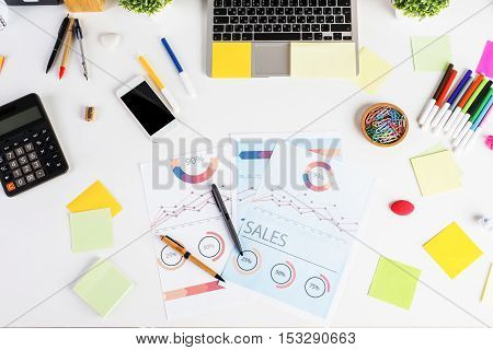 Top view of white desktop with financiqal report calculator colorful supplies blank cellular phone laptop keyboard and other items. Accounting concept
