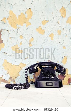 Vintage rotary phone, wall with chipped paint
