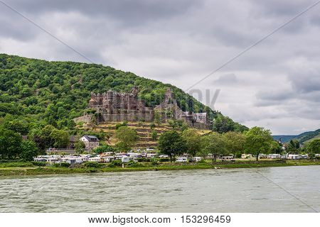 Trechtingshausen Germany - May 23 2016: Reichenstein castle and Camping Marienort in cloudy weather on the Rhine Gorge near Trechtingshausen Rhine Valley Rhineland-Palatinate Germany UNESCO World Heritage Site.