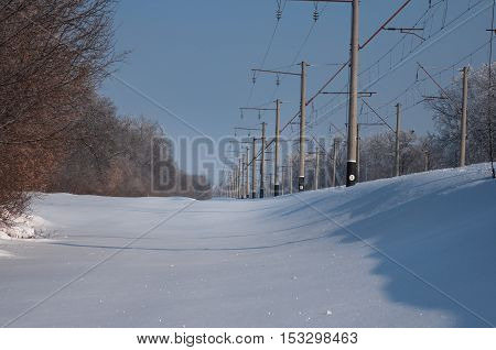 Railway power lines supports and wires on a clear winter blue sky background and forest