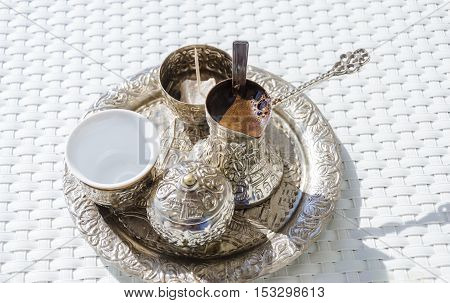 A metallic tray with copper plated cezve (džezva) filled with traditional foam Bosnian coffee a silver pot with turkish delight rahat lokum a clay cup and sugar cube pot served in an ornament Sarajevo set. poster