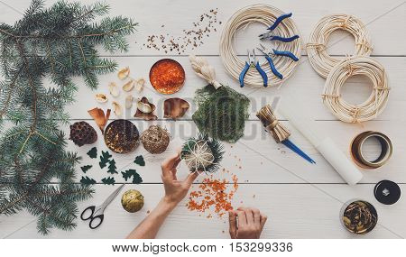Creative diy craft hobby. Making handmade craft christmas ornaments, garland and balls. Woman's leisure, tools and trinkets for holiday decorations. Top view of white wooden table with female hands.