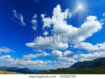 Blue Sunshiny Sky With White Clouds Over Mountain.