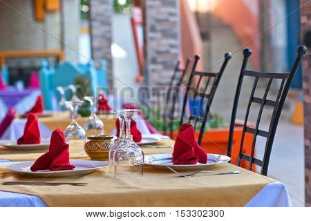 Covered dining table in restaurant with wine glasses