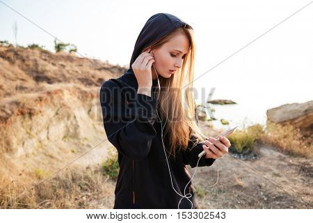 Portrait of a young fitness woman in black hoodie listening music with earphones and smartphone outdoors at the beach