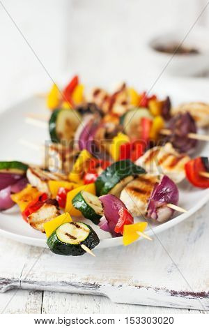Closeup of chicken skewers or shashlik with grilled vegetables (mushrooms paprika salad zucchini onion)
