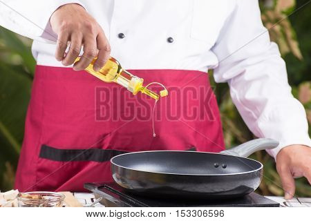 Chef pouring vegetable oil to the pan / cooking stir fry vegetarian noodle concept