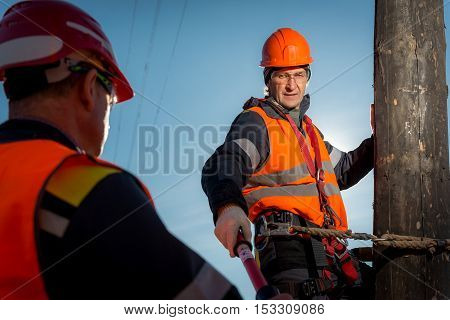 RUSSIA - OCTOBER, 2016: Electrician lineman repairman worker at climbing work on electric post power pole