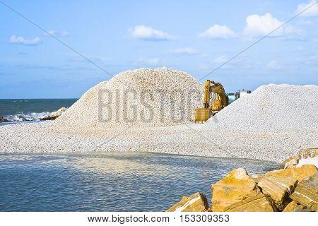 Diggers on the seashore building a breakwater