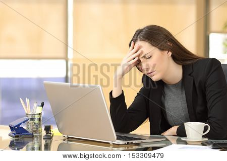 Businesswoman suffering migraines at job working on line with a laptop sitting in a desktop at office