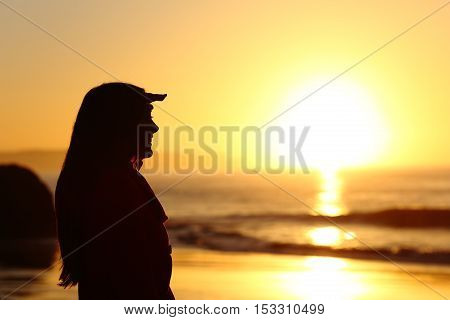 Side view of a hopeful woman silhouette looking forward with the hand on forehead at sunset with the sun horizon and sea in the background