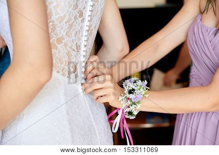 bride wearing wedding white dress. helping the bride to put her. bridesmaids dress laces on the back. tying bow