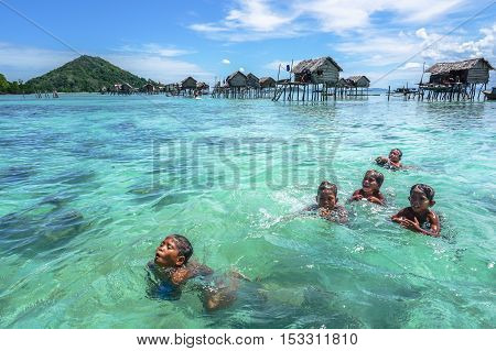 Semporna,Sabah-Sept 10,2016:Sea Gypsy Children playing & swimming in the ocean on 10th Sept 2016 at Semporna,Sabah.Sea Gypsy children are given a net & taught to catch fish,octopus & lobsters.