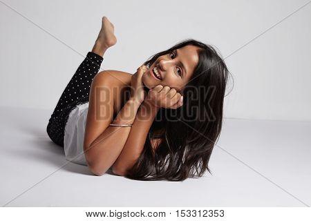 Happe Smiling Woman Lies Down On White Floor In Studio