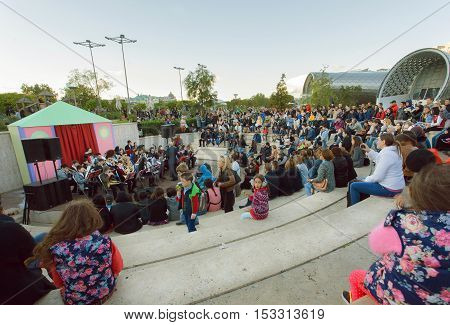 TBILISI, GEORGIA - OCT 15, 2016: Crowd of young people sitting on a concert of an orchestra at park Rike during festival Tbilisoba on October 15, 2016. Tbilisoba is traditional festival in Tbilisi from 1979