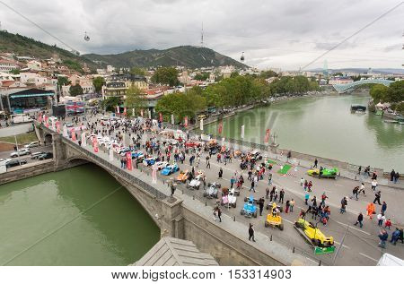TBILISI, GEORGIA - OCT 15, 2016: Crowd of people watching the outdoor exhibition of retro cars on the old bridge through Kura River on October 15, 2016. Tbilisi has a population of 1.5 million people