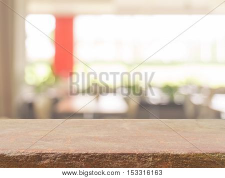 Stone board empty table top on of blurred background. Perspective brown stone over blur in coffee shop background - can be used mock up for montage products display or design key visual layout.