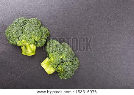 inflorescence of raw broccoli on a slate board top view