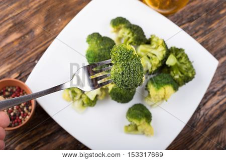 Boiled broccoli on a plate One inflorescence cabbage on a fork healthy eating diet Ducane