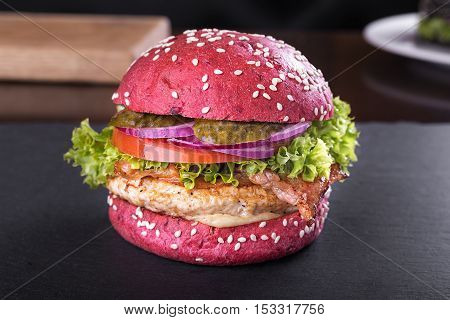 Red burger with cutlet bacon and vegetables sprinkled with sesame seeds on a blackboard